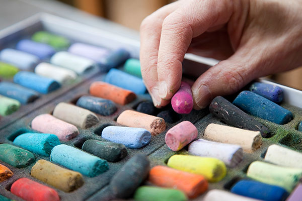 close up of a hand selecting pastels